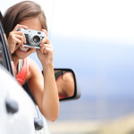 Woman tourist taking photo in car with camera driving on road tr